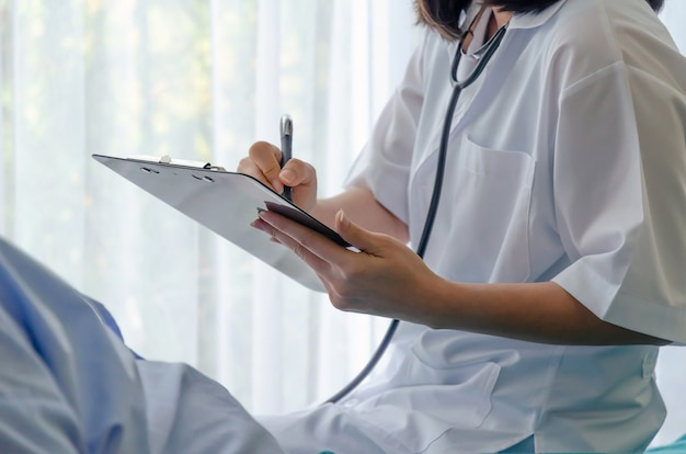 Доктор почерков буфер обмена и проверка старого пациента, лежащего на кровати в больнице для поощрения