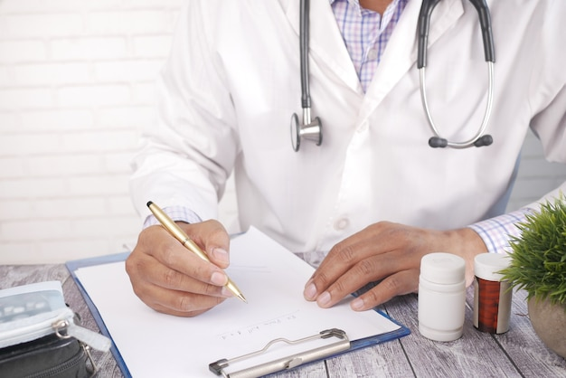 Doctor hand writing prescription on clinic desk with pill contianer on table