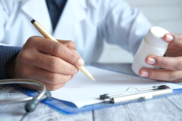 Doctor hand writing prescription on desk, close up.
