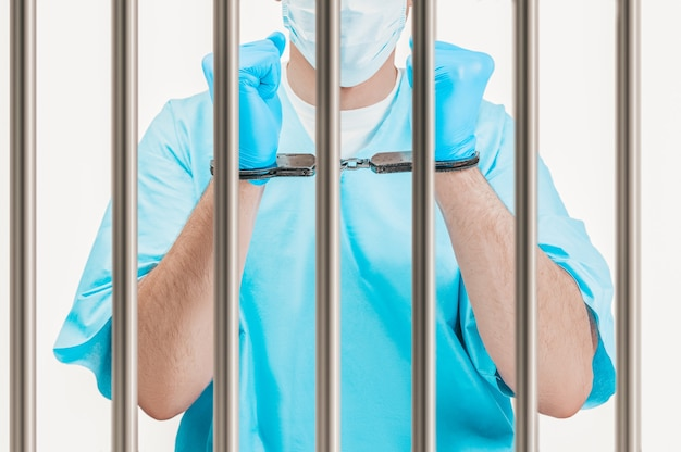 Doctor in handcuffs is standing behind a prison cell. the concept of corruption in medicine