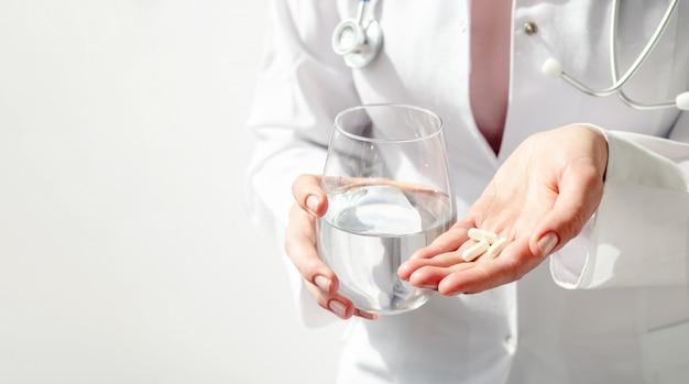 Доктор руки, давая белые таблетки и стакан воды.