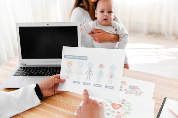 生まれたばかりの赤ちゃんの図を保持している医師の手