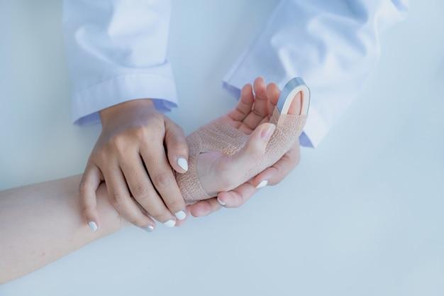 健康診断の結果を奨励し、説明するために腕の事故で患者を保持している医師の手