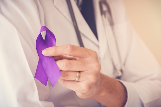 Doctor hands holding purple ribbon, alzheimer disease, epilepsy awareness