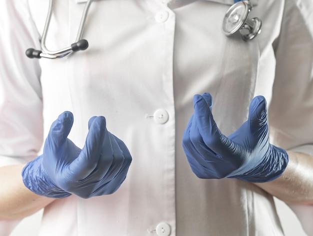 청진기와 제복을 입은 smth 의료진 전문가를 설명하는 장갑 근접 촬영 의사의 손을 닫습니다.