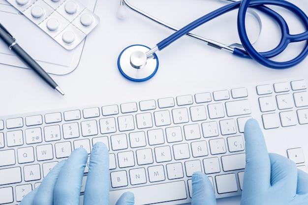 화이트 책상에 컴퓨터 키보드에 입력하는 장갑에 의사 손. 원격 진료 또는 의료 기술 개념 배경. 평면도