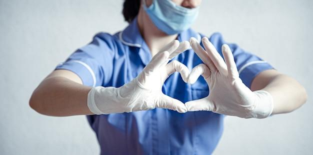 医者はラテックス手袋を手に取り、心臓のシンボルを示します。心臓の医者。私たちの医療専門家が大好きです。