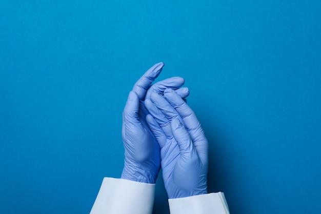 파란색 격리 된 배경에 의료 장갑에 의사 손
