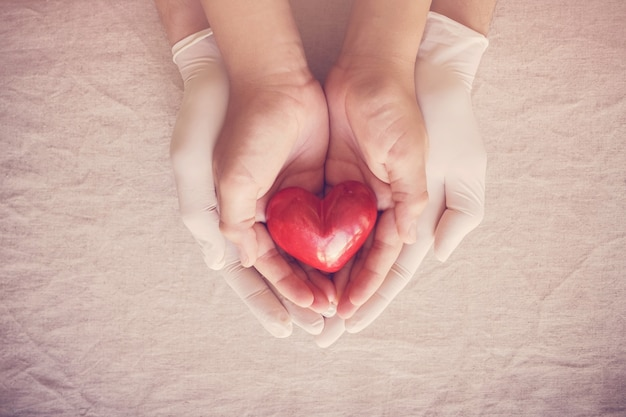 Doctor hands with gloves holding child hands, red heart, health insurance, donation concept