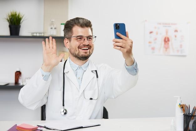 医師が医療キャビネットで患者とビデオ通話をし、医療ユニフォームを着た男性セラピストが聴診器を備えた医療キャビネットに座って、スマートフォンを使用してwebでオンライン相談を行っている