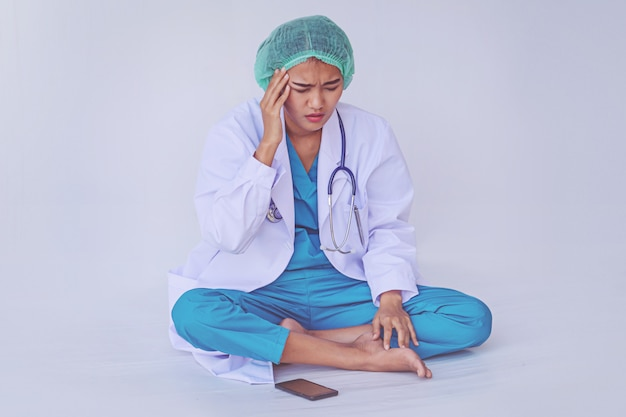一生懸命働いて、白い背景の上のストレスから医師の頭痛。
