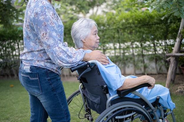 Помощь и уход доктора азиатский пожилой или пожилой пациент пожилой женщины сидит на инвалидной коляске в парке в палате медсестры, здоровая сильная медицинская концепция.