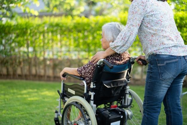 医師の助けとケア看護病棟の公園で車椅子に座っているアジアの高齢者または高齢の老婦人女性患者、健康的な強力な医療コンセプト。