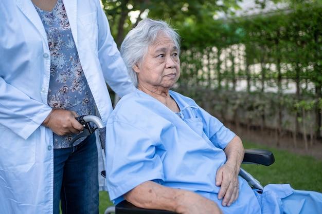 公園で車椅子に座っているアジアの高齢者または高齢の老婦人女性患者の医師の助けとケア