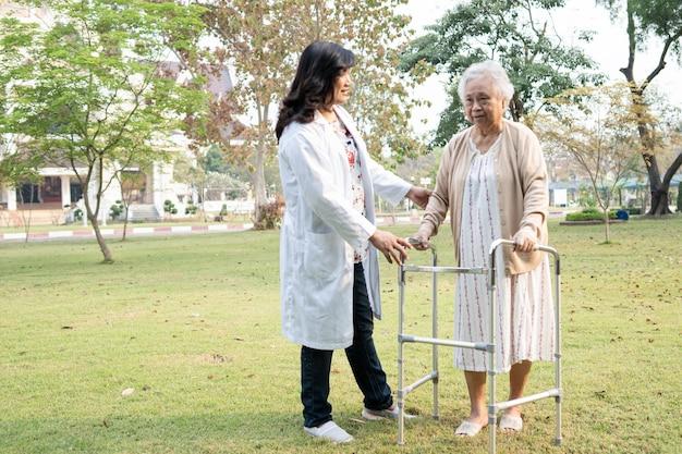 医師の助けとケアアジアの高齢者または高齢の老婦人女性は、幸せな新鮮な休日に公園を歩いている間、健康の強い歩行器を使用しています。