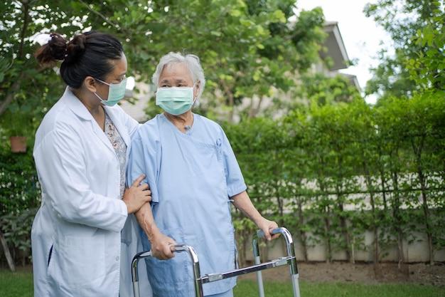 医師の助けとケアアジアのシニアまたは高齢の老婦人女性は、幸せな新鮮な休日に公園を歩いている間、健康の強い歩行器を使用しています。