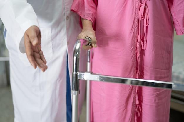 医師の助けとケアアジアの高齢者または高齢の老婦人女性は、病院を歩いている間、健康の良い歩行器を使用しています。