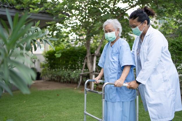 医師の助けとケアアジアの高齢者または高齢者は公園で歩行器を使用します