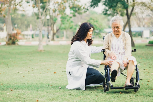 医者は公園で車椅子に座っているアジアの年配の女性患者を助け、世話をします。