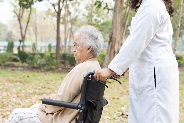 의사의 도움과 관리 아시아 수석 여자 환자가 공원에서 휠체어에 앉아
