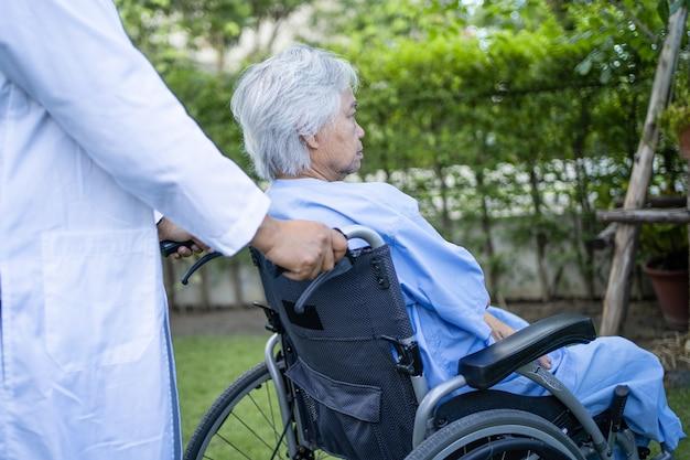 医師の助けとケア公園で車椅子に座っているアジアの年配の女性患者