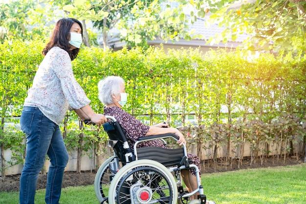 公園で車椅子に座っているアジアの年配の女性患者の医者の助けとケア