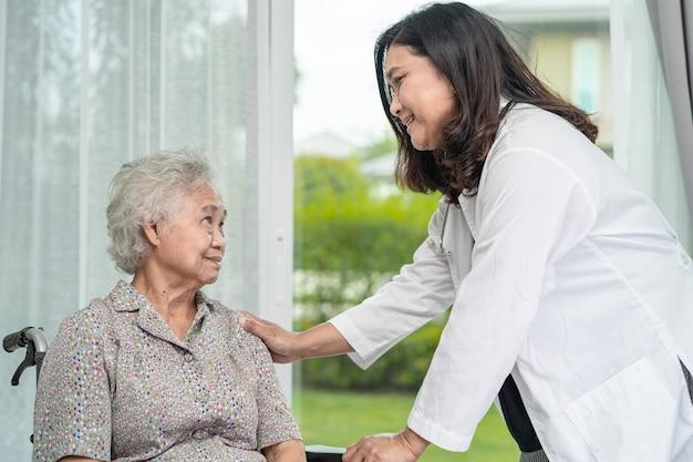 車椅子に座っているアジアの年配の女性患者の医者の助けとケア