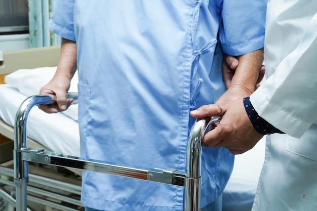 医師の助けとケアアジアの年配の女性が歩いている間ウォーカーを使用します。