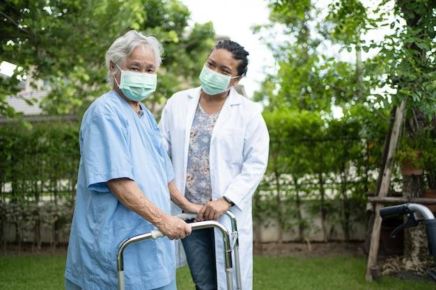 医者の助けとケアアジアの年配の女性は公園で健康の強い歩行器を使用します