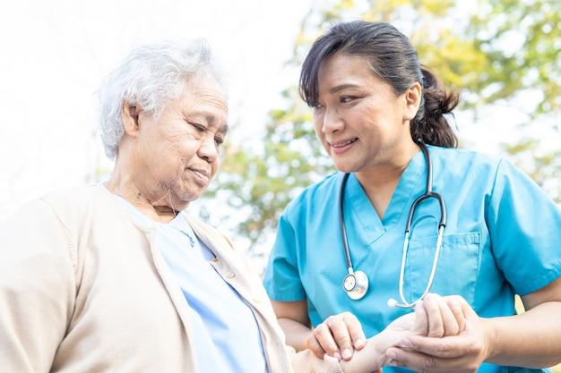 医者の助けとケア公園で歩くアジアの年配の女性