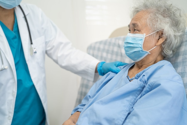 Doctor help asian senior or elderly old lady woman patient wearing a face mask protectcoronavirus