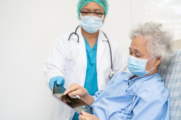 医師は、安全感染を保護し、covid-19コロナウイルスを殺すために病院でフェイスマスクを着用しているアジアの高齢者または高齢の老婦人女性患者を助けます。