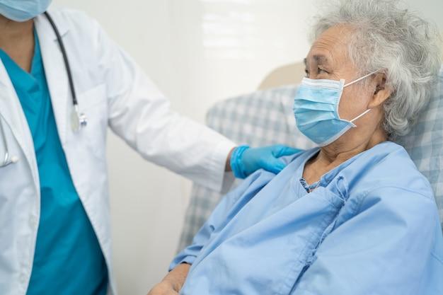医師は、フェイスマスクを身に着けているアジアの高齢者または高齢の老婦人女性患者がコロナウイルスを保護するのを助けます
