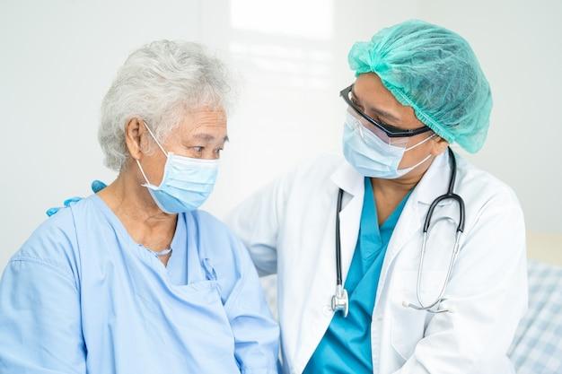 医師はコロナウイルスを保護するために病院でフェイスマスクを着用しているアジアの年配の女性患者を支援します