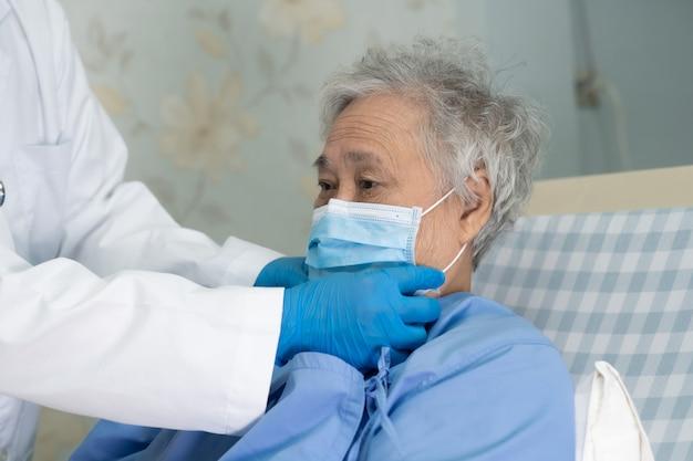 의사는 병원에서 얼굴 마스크를 쓰고 아시아 수석 여자 환자가 covid-19 바이러스를 보호하도록 도와줍니다.