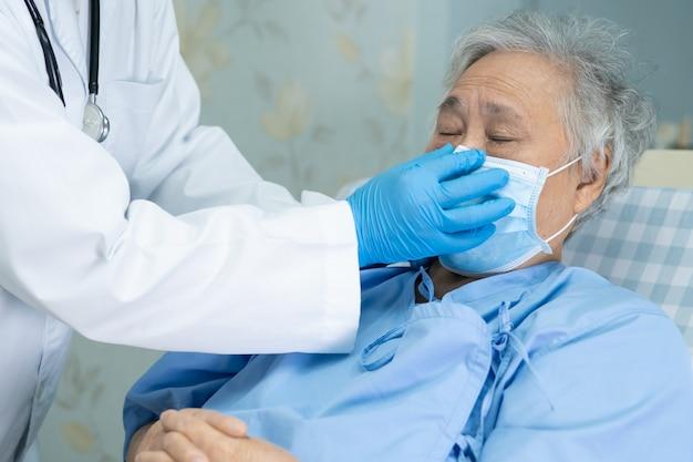 Помогите доктору азиатский старший пациент женщины нося лицевой щиток гермошлема в больнице для защищает вирус covid-19.