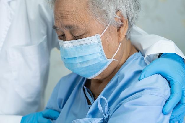 Врачуйте помощь азиатскому старшему пациенту женщины нося лицевой щиток гермошлема в больнице.