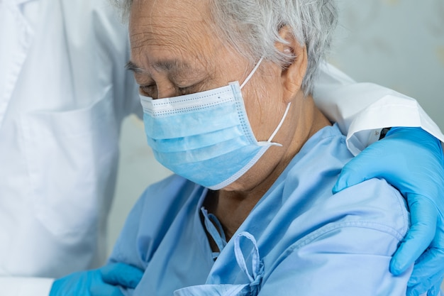 Doctor help asian senior woman patient wearing a face mask in hospital.