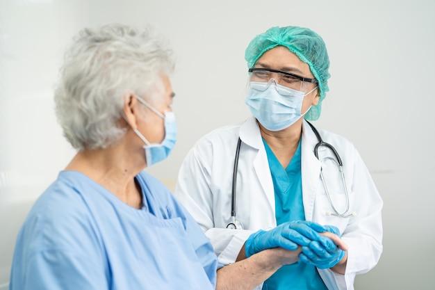 医師はコロナウイルスを保護するためのマスクを身に着けているアジアの年配の女性患者を助けます