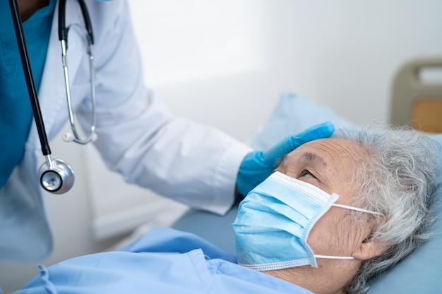 Doctor help asian senior woman patient wearing mask in hospital for protect coronavirus