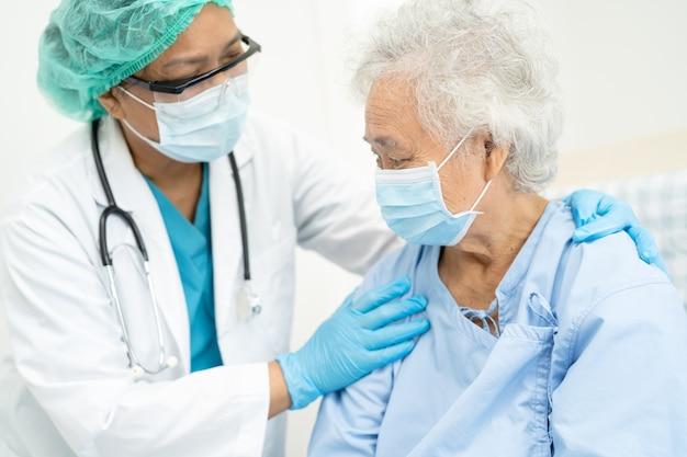 医師は、コロナウイルスを保護するために病院でマスクを着用しているアジアの年配の女性患者を支援します