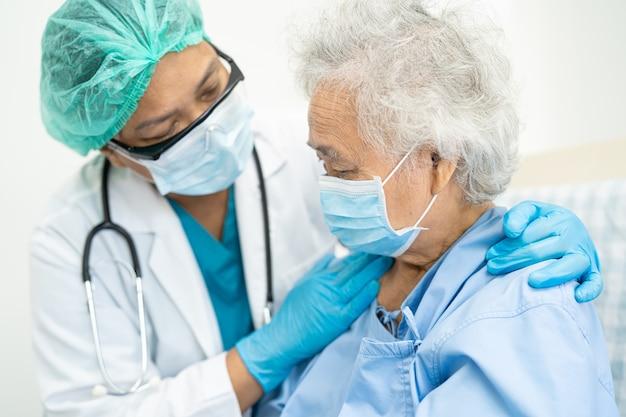 医師はコロナウイルスを保護するために病院でマスクを着用しているアジアの年配の女性患者を支援します
