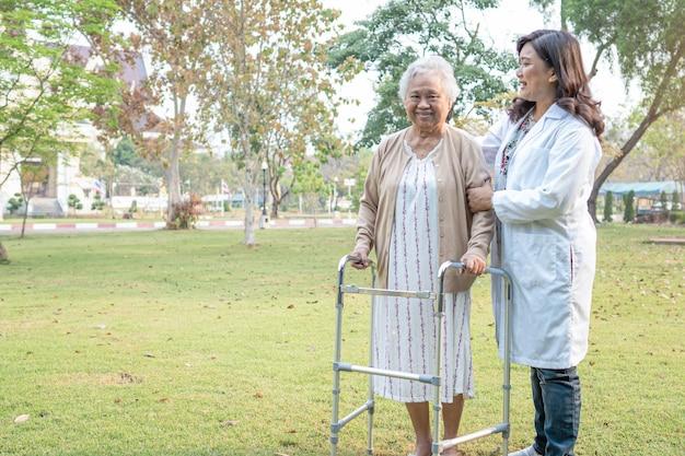 医者はアジアの年配の女性が公園で歩行器を使用するのを手伝います。