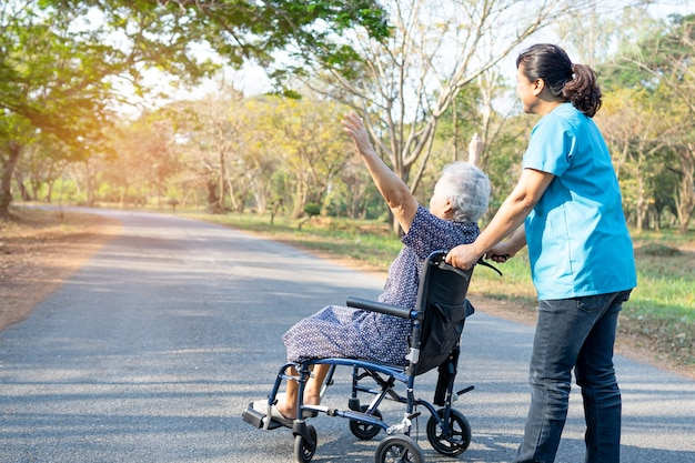 Doctor help and care asian senior or elderly old lady woman patient sitting on wheelchair at park in nursing hospital ward, healthy strong medical concept.