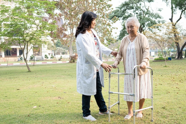 Doctor help and care asian senior or elderly old lady woman use walker with strong health while walking at park in happy fresh holiday.