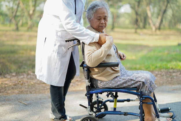 Doctor help and care asian senior woman patient sitting on wheelchair in park.