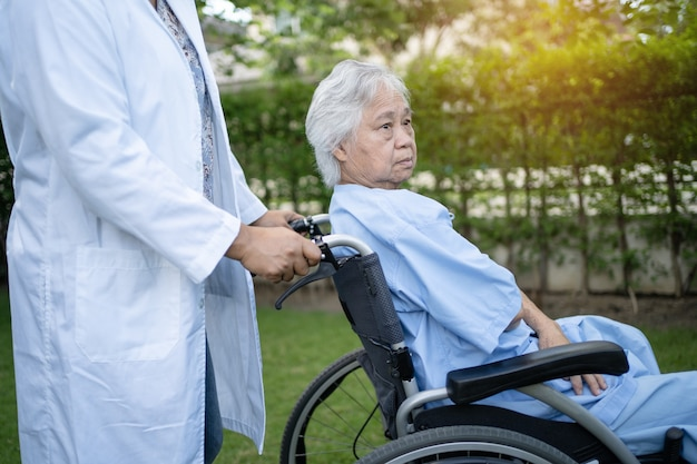 Doctor help and care asian senior woman patient sitting on wheelchair at park