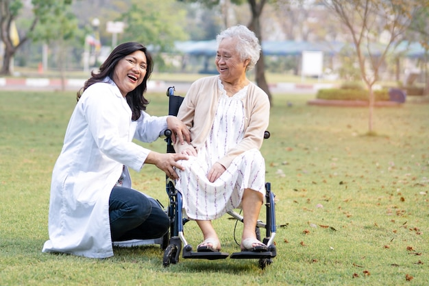 Doctor help and care asian senior woman patient sitting on wheelchair with happy at park