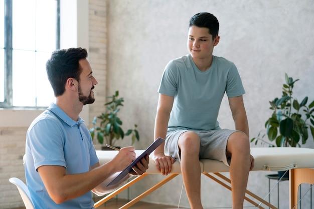 물리 치료 중간 샷에서 소년을 돕는 의사