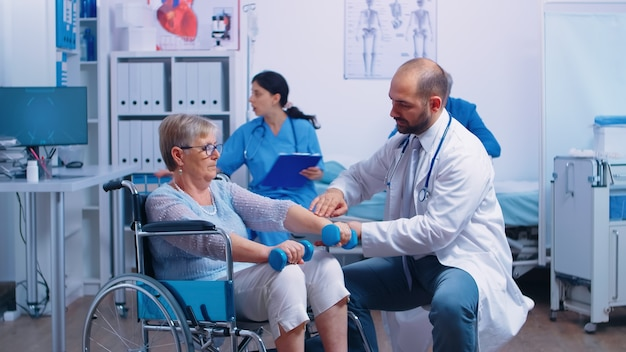Doctor helping disabled senior patient to recover muscle strength in private modern rehabilitation clinic or hospital. nurse in background talking with elderly man with walking frame